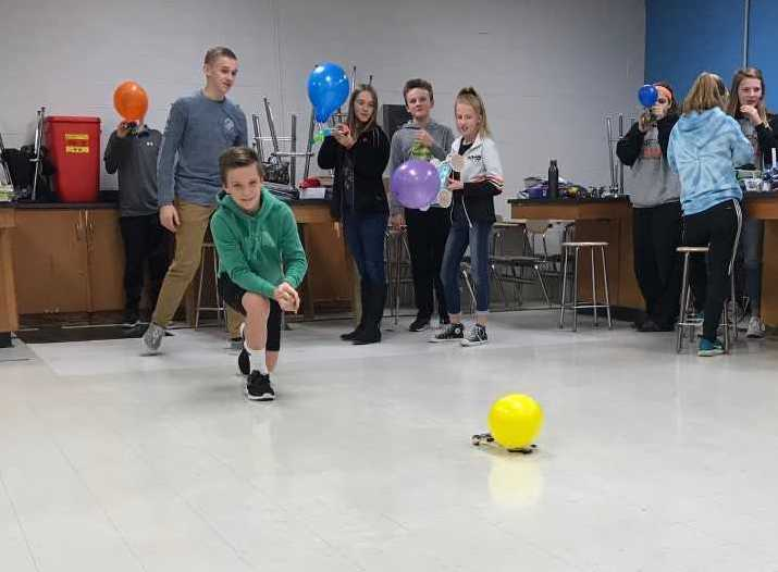 students sending a balloon car across a room